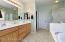 With Upgraded Diagonal Floor Tile, Oval Bathtub with Marble Surround, Upgraded Rain Glass Enclosed Shower, Marble Vanity with Dual Sinks, Oak Cabinetry, Mirrored Medicine Cabinets, Private Toilet Room, Big Glass Block Window & Pleated Shade.