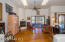 Central living space opens to the back covered patio. Features 2 skylights, ceiling fan, corner fireplace, wood shutters, engineered wood floors ++ low pony wall separating area from Entry & adjacent Dining