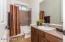 Deep Tub/Shower with Marble Sandstone Surround + Sandstone Vanity Counter, Raised Sink, Tiled Flooring & Mirrored Medicine Cabinet.