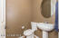 Guest Powder Room with Pedestal Sink, Dual Flush Toilet, Oval Mirror, tile Flooring & 2 Tone Paint