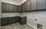 Spacious Inside Laundry Room with Deep Utility Sink, Designer Soft Close Cabinetry with Pulls, Beautiful Plank Style Tile Flooring with Exterior Mud Room Entrance.
