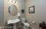 Nice Powder Room for Guests with Oval Mirror, Tiled Flooring, Upgraded Lighting & 2 Tone Paint.