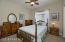 Good Sized Guest Bedroom w/ Lighted Ceiling Fan, Sunny Window w/Horizontal Blinds & Drapes, Carpet Flooring & Sliding Door Closet.