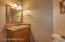 Sink in guest bath with rustic lighting fixture and matching cabinets through out.