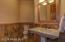 Half bath with slate back splash and flooring. Pedestal sink and wood framed mirror.