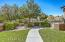 with Nice Walking Path, Boulder Accents, Block & Iron View Fencing, Shade Trees, Auto Watering Drip System & Faux Grass Lawn.
