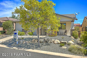 with Nice Covered Front Patio w/Mountain View, Hardi Board Siding, Stacked Rock Accents, Mature Shade Tree, Solar Path Lights, Boulders & Easy Care Drip Watering System.