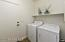 Inside Laundry Room with Washer & Dryer, Travertine Stone Flooring & Deep Utility Closet.