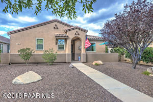 Spanish Style Single Level Home with Concrete Tile Roof, Easy Care Drip Landscaping, Boulders, Plants, Pretty Shade Trees, Covered Front Entry & Open Front Coffee Patio.