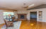 Living room with brick fireplace, custom wood floors, and art niches