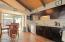 Cathedral ceilings and a kitchen basked with natural lighting