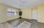 Great Room with Wood Look Laminate Flooring, Media Niche, Wall of Sunny Windows w/Horizontal Blinds, Ceiling Fan & Direct Access to the 2 Car Garage.