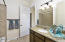 """with Tall Granite Counter, Under-mount Sink Beveled Edge Mirrored Medicine Cabinet, Hardwood Cabinetry, Elongated Toilet, Tiled Shower/Bath Combo with 18"""" Floor Tile, Bronze Rubbed Oil Lighting & Shower Curtain Bar."""