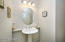 with Tile Flooring, Oval Mirror, Pedestal Sink & Elongated Toilet.