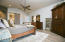 Master bedroom on the main level with tile flooring and barn door for privacy.