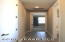Hallway to left of Entry Foyer leads to large storage closet, Guest Bath and Guest Bedroom.