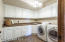 A dream laundry space with loads of cabinets, w/d included and utility sink.