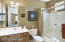 with Full Tub/Shower combo, Clear Glass Sliding Doors, Marble Sink, Accent Window, Mirrored Medicine Cabinet & Tiled Flooring.