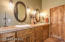 A double sink vanity with Travertine Tile countertops.