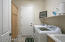 with Plank Tile Flooring, Deep Utility Sink, Laundry Shelf, Hardwood Storage Cabinetry, Folding Counter & 3 Laundry Bins.