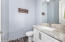 Powder room or half bath is thoughtfully positioned in hall for easy guest use.