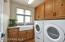 Laundry room features built in cabinets and a gorgeous farmhouse style sink.