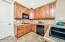 Nice Upgraded Kitchen with Black Appliances, Gas Stove, Wall Oven, Refrigerator, Full Tile Counters & Tiled Back-splash, Knotty Alder Cabinetry, Under Counter Lighting, Tile Flooring, Dining Bar & Pantry.