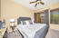 Main Floor Spacious Master Bedroom with Carpet Flooring, Lighted Ceiling Fan, 2 Tone Paint, Sunny Windows with Wood Horizontal Blinds, Sliding Doors to Rear Yard Patio, Black-out Drapes & Walk In Closet.