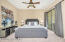 Main Floor Spacious Primary Bedroom Suite with Carpet Flooring, Lighted Ceiling Fan, 2 Tone Paint, Sunny Windows with Wood Horizontal Blinds, Sliding Doors to Rear Yard Patio, Black-out Drapes & Walk In Closet.
