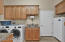 Laundry with utility sink, folding counter, freezer stays, a closet and built in ironing board