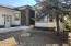 Large front yard with native mature trees and low maintenance gravel.