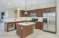 Light and Bright Kitchen includes Center Island w/Pendant Lighting, Gas Stove & Stainless Steel Refrigerator.