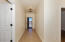 Entry hall to home with second bedroom and laundry room with garage access across hall.