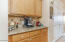 with Blond Hardwood Cabinetry, Under Cabinet Lighting, Tiled Backsplash & Granite Counter.