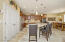 """with Large Granite Dining Island, Full Granite Backsplash, Pendant Lighting, Under Cabinet Lighting, Recessed Lighting, Beechwood Cabinetry, 20"""" Tile Flooring, Double Door Pantry, Staggered Cabinetry with Stainless Appliances + Refrigerator, Gas Cooktop, Wall Oven & Microwave w/Convection, Dining Area with Sunny Window to Rear Yard."""