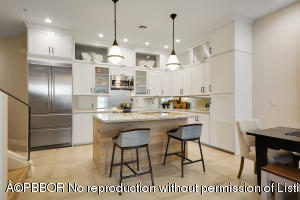 Designer eat-in kitchen with granite countertops, Liebherr refrigerator/freezer, custom lighting and cabinetry