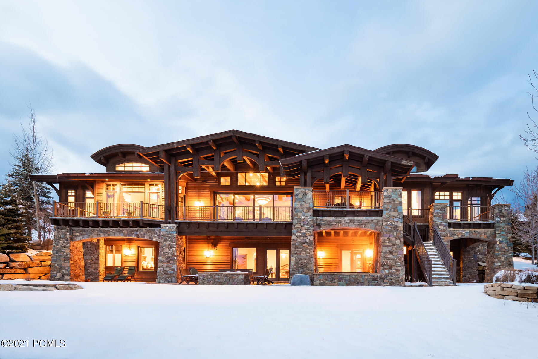 This sophisticated mountain residence embodies refined rustic elegance with panoramic ski run and mountain views. Thoughtfully designed by renowned architect Michael Upwall, the residence features his signature touch with a flowing, functional layout ideal for multi-generational enjoyment. The customization implemented by acclaimed designer Paula Berg is unmatched, tastefully coordinated with custom finishes, and meticulous attention to detail. From the reclaimed Wisconsin schoolhouse floors to thoughtfully designed furniture perfectly created to nest along luxurious curved walls, this property will impress the most discerning of Buyers. The sprawling main level includes a luxurious master suite, two additional guest suites, and a handsomely crafted private office. The main level living area showcases impressive interior design elements, including an elevated circular dining area fit for royalty. The chef's kitchen includes a dramatic copper hood, hand-selected hardware, commercial-grade appliances, and an oversized island to accommodate preparation for large gatherings with family and friends. The intimate breakfast nook is the perfect place to share a meal by one of the 8 fireplaces throughout the home. Invite friends and family for extended stays where they can feel at home in one of the three lower-level guest suites. After a day of mountain adventures, your guest can enjoy their favorite flicks in the Sundance-inspired theatre room, relax at the bar or enjoy a steam in the private home gym. This centrally located home includes a coveted full golf membership and is within walking distance to The Ranch and Dye Clubhouse's allowing the homeowner to enjoy Promontory's many amenities with ease. Welcome home to Painted Sky!