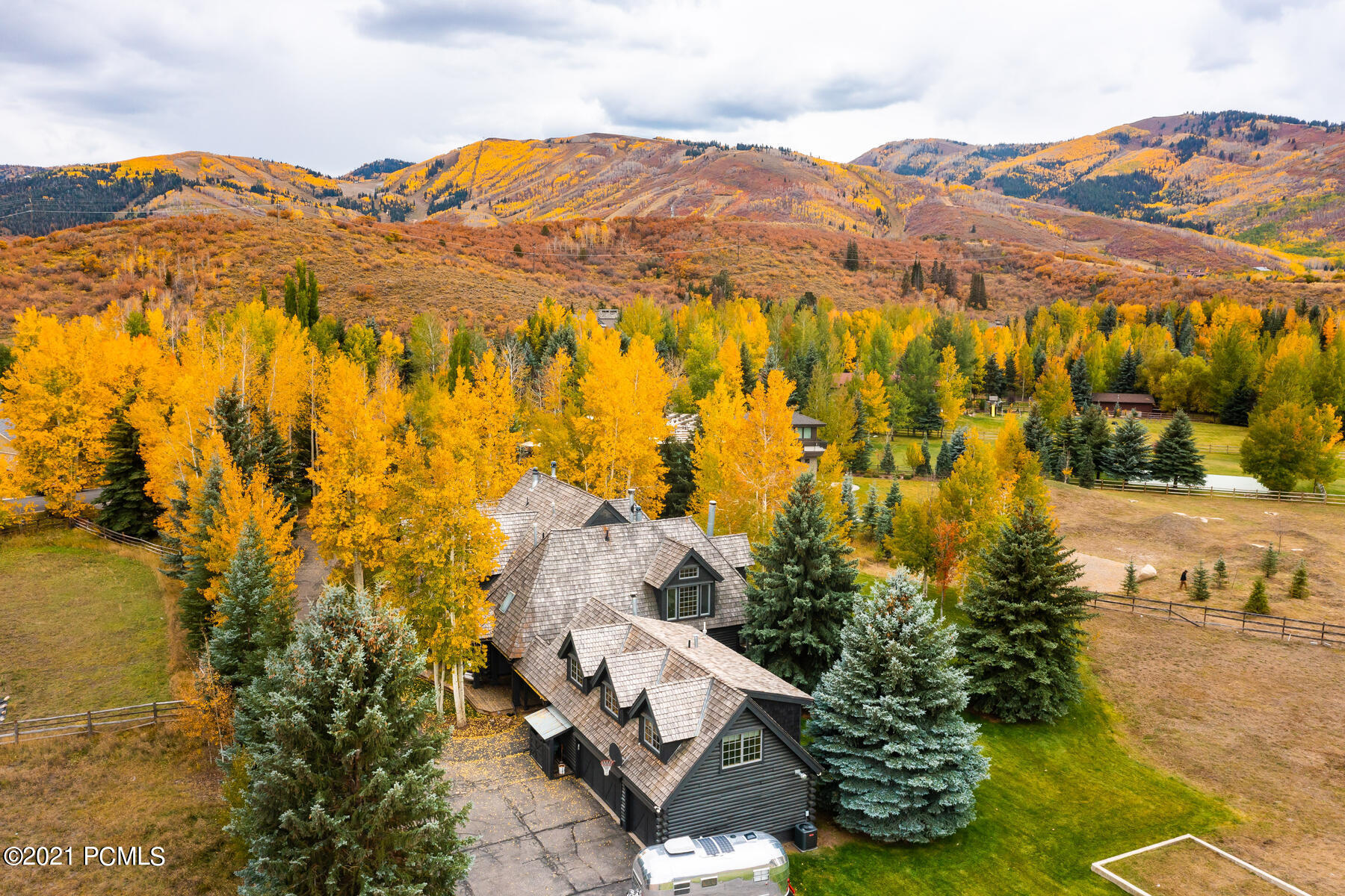 Aged pines and multi-colored aspens adorn the private drive leading to this gorgeous Scandinavian style ranchette on 1.64 acres in the heart of Park Meadows remodeled in 2020 with panoramic views of Park City Mountain Resort. The highly sought-after equestrian zoned lot is walking distance from Park City schools, minutes from the slopes, and a short stroll into town while still feeling like you are miles away in the countryside. A crisp, clean palette compliments the warm hardwood floors, ceiling beams, and stone fireplaces highlighted by large windows and custom lighting. Two oversized family rooms on the main level are adjacent to the large chef's kitchen and dining area, all centered with wood-burning fireplaces. Enjoy the ultimate in all seasons relaxation on your wrap-around porch which has several access points for year-round alfresco dining, lounging with friends, or soaking in your recessed hot tub. The first-floor wing enjoys its own entrance with three bedrooms, two bathrooms, and laundry making it ideal for guests. The grand master suite features a spacious spa bathroom with a soaking tub, steam shower, and heated floors, a den with a gas fireplace and balcony with mountain views, and a large walk-in closet with laundry. A separate guest house has a bedroom and bathroom, a living area, a newly updated kitchen, and is surrounded by lush landscaping that maximizes its dramatic setting. The ultimate combination of location, amenities, and views from this peaceful oasis is a rare opportunity in Park City that will delight family and friends for generations.