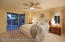 master bedroom with ceiling fan and sliding glass door to rear yard and patio
