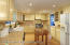 large kitchen with custom cabinets, recessed lights and built-in wine cooler