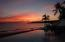 Sunset behind beachfront infinity pool