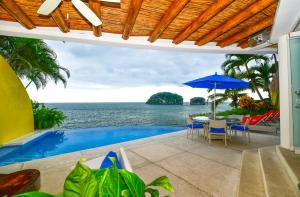 The architectural signature in this 4 bedroom waterfront villa stands apart from its peers.  All living spaces captivate ones eyes with the view of los arcos,  all  seemingly  in reaching distance.The light filled generous spaces are all decorated with colorful elements that make one aware of the relaxing vacation residence this is.Complete with garage and caretakers apartment, up to date with federal maritime zone concessions.