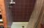 Tile shower in pine bathroom