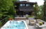 rooftop deck with pool/hot tub/outdoor living area with outdoor kitchen in the back by main home