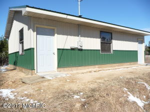 New in 2016. Framed for a garage door, the pole barn sits at the rear of Unit 3.