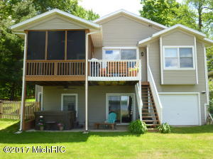 House view from 70' of Wall Lake waterfront. Multiple outdoors living areas include: screened-in porch, upper level deck with grill and seqting area, lower level cement patio with hot tub all overlooking the lake front.
