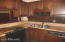 Jennaire stove, dishwasher, and a double sink are surrounded by handsome cabinets.