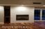 Tiled gas log fire place with video/sound cabinets to the left.