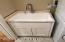 Laundry tub in custom base cabinet with granite top.
