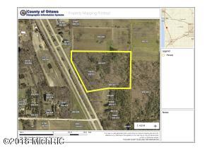 Great spot for possible commercial acreage on US-31. Located between Grand Haven and Holland with more traffic than you can ask for. Approximately 23 acres, mostly wooded with existing ranch home. Road frontage on highway is 775'. Timber could be sold and cleared for berry farming, could be lotted off to make a great sub division for homes, camp ground or small manufacturing business. Existing home could be used as office or live there while you run your business. Homes shows great and is move in ready. Call today for more information. **Acreage is in 3 parcels sold together.  Township approval needed for commercial zoning.